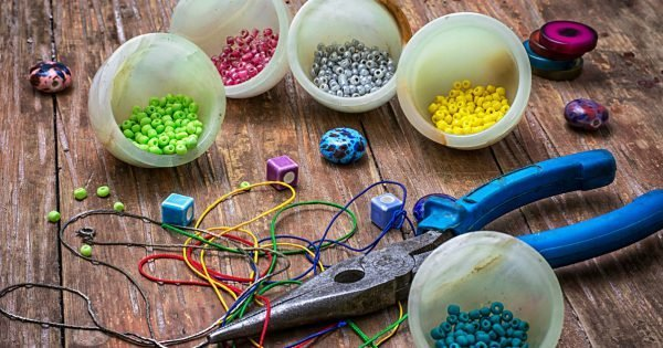 coil,beads and tools for needlework on turquoise wooden background
