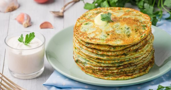 Many pancakes with fresh herbs and sour cream sauce on a wooden table. Traditional Ukrainian or Russian pancakes. Maslenitsa. Traditional dishes on the holiday Carnival Maslenitsa Shrovetide.