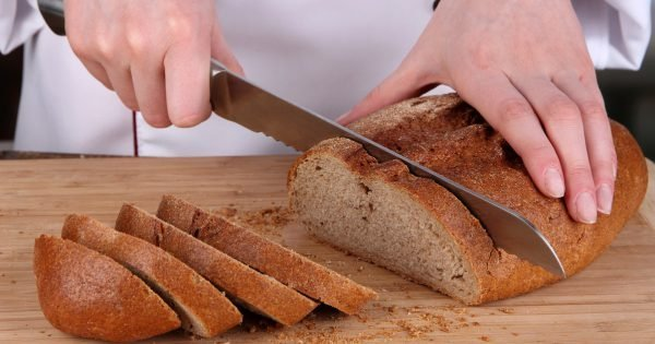 Cutting bread on wooden board close up