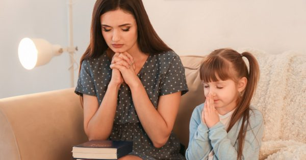 Religious Christian girl and her mother praying at home