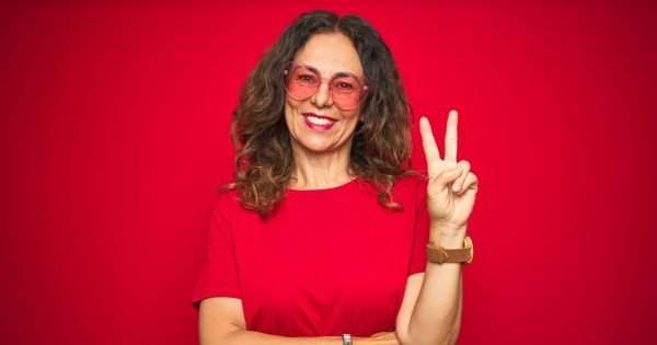 Middle age senior woman wearing cute heart shaped glasses over red isolated background smiling with happy face winking at the camera doing victory sign. Number two.