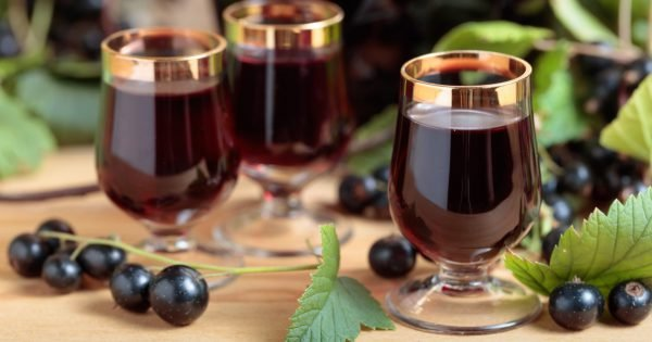 Homemade black currant liqueur and fresh berries on a branch , wooden background.