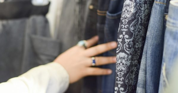 Hand browsing racks of shirts and pants at a stylish boutique