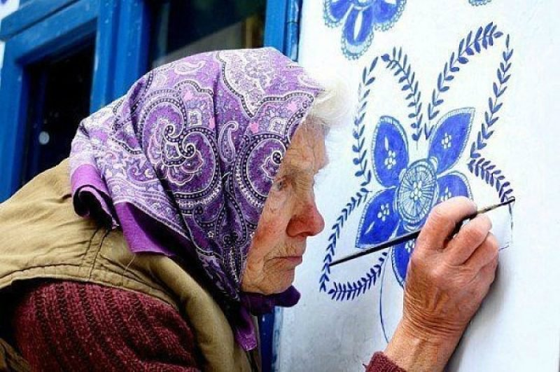 старушка расписывает стену