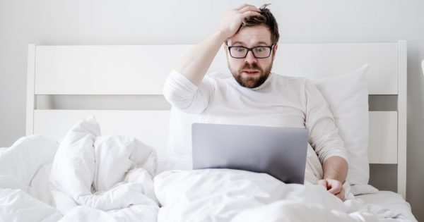 Upset man with a laptop in bed received bad news, he is confused, holding hand to his head and watching the screen in shocked eyes.