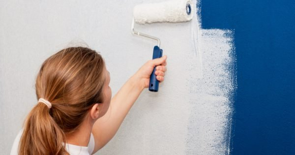 Woman painting interior wall of house with a roller