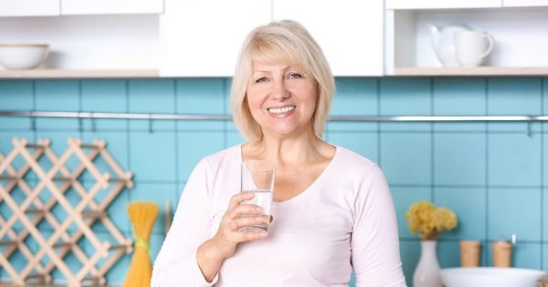 Beautiful mature woman drinking water in kitchen