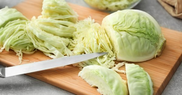 Wooden board with cut cabbage on table
