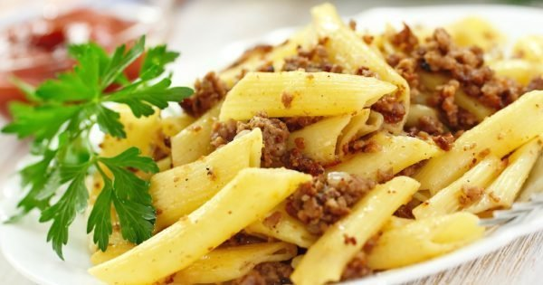 Pasta with fried meat, sauce and fresh vegetables