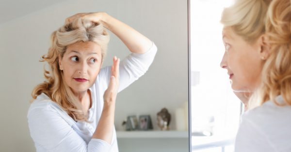 Senior beautiful woman checking her hair in front of mirror at home.