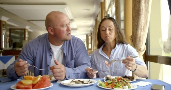 The husband bald and in glasses and the dark-haired middle-aged wife, sit in cafe, eat, treat each other, estimate food, laugh, communicate. Have them on the table are worth fruits, vegetables and hotter.