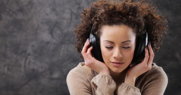 Young beautiful woman listening to music with headphones
