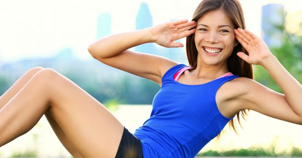 Exercise woman doing situps in outdoor workout training. Asian sport fitness woman smiling cheerful and happy looking at camera