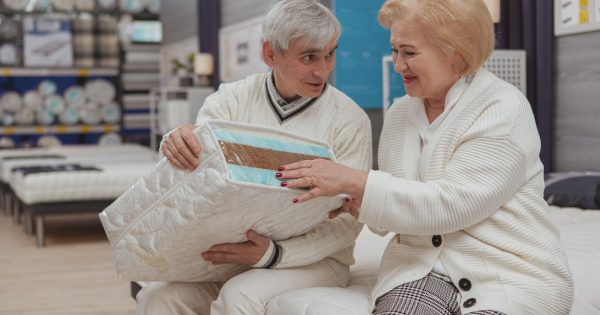 Charming senior woman laughing joyfully, shopping for new orthopedic mattress with her loving husband. Cheerful elderly couple discussing mattress sample, sitting on a bed at furnishings store