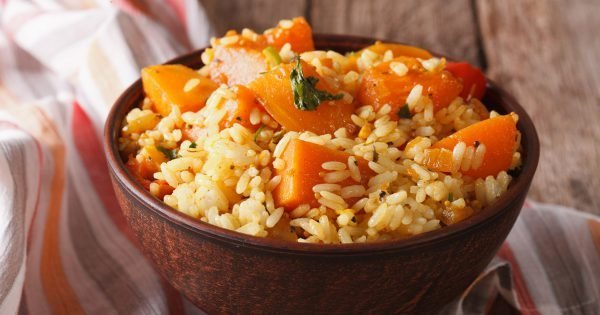 Vegetarian food: rice with pumpkin in a bowl on the table. Horizontal