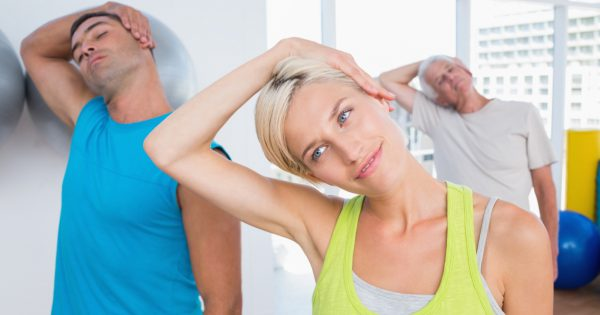 Woman with friends doing neck exercise in fitness club