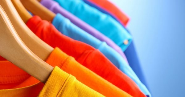 Lots of T-shirts on hangers on blue background