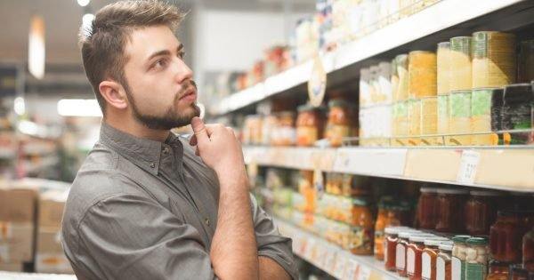 Buyer man looks at the supermarket shelf and thinks what product to take. Buyer selects canned food at the store. Shopping in a supermarket.