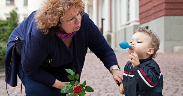 grandmother is thaking care of a smoll boy outdoors
