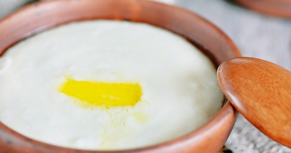 Semolina porridge with melted butter in the clay plate