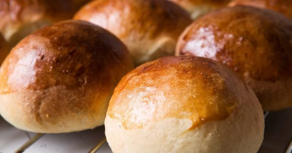 Close up detail of freshly baked hot cross buns in romantic renaissance lighting and a shallow depth of field.