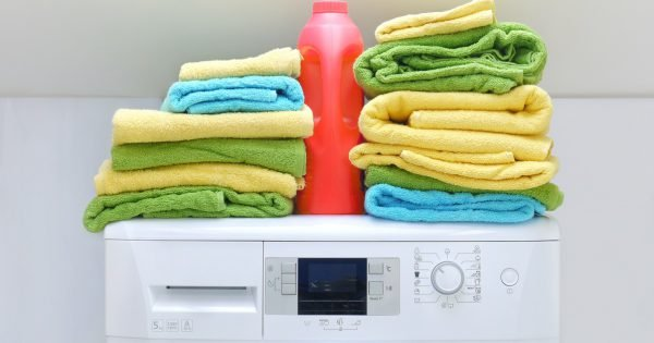 Pile of fresh colorful towels and bottle of detergent on washing machine