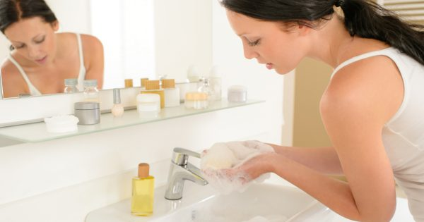 Young woman in bathroom washing her hands with soap bar