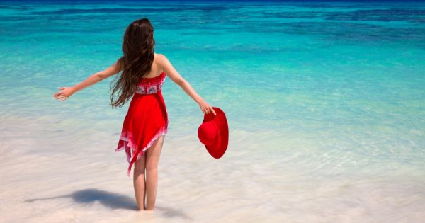 Happy woman enjoying on exotic beach in summer by tropical blue water. Attractive girl in red dress resting, outdoor portrait. Bliss freedom concept. Travel.