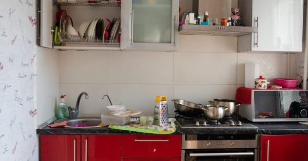 Belarus Minsk 06 12 2019 Typical small kitchen with dirty dishes and clutter full shot. Disgusting heap of crockery empty filthy cuisine during cooking cook room before cleaning