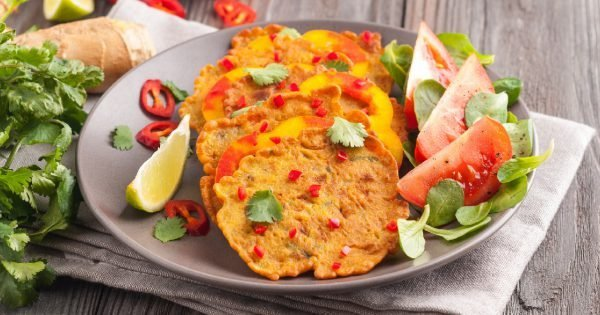 Indian chickpea crepes Pudla served on a plate with tomatoes, lime, cilantro, mash (mung bean) salad, chilli, ginger, bell pepper. Copy space.