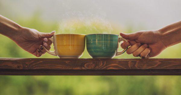 Hands holding mug with hot beverage, with tea on a wooden stand outdoors in the countryside