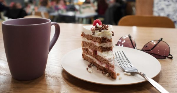 Still life in a cafe. A Cup of coffee or tea, the plate of half-eaten cake. To give up sweets.