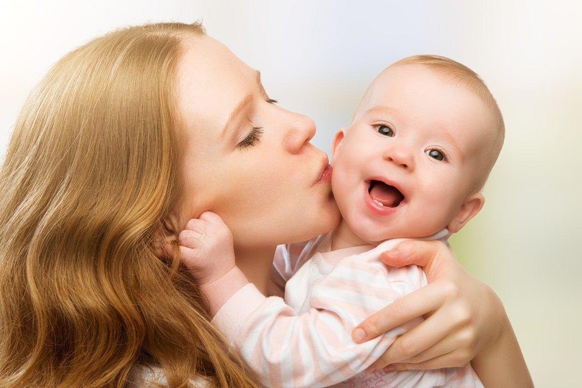 щаслива мама цілує дитину