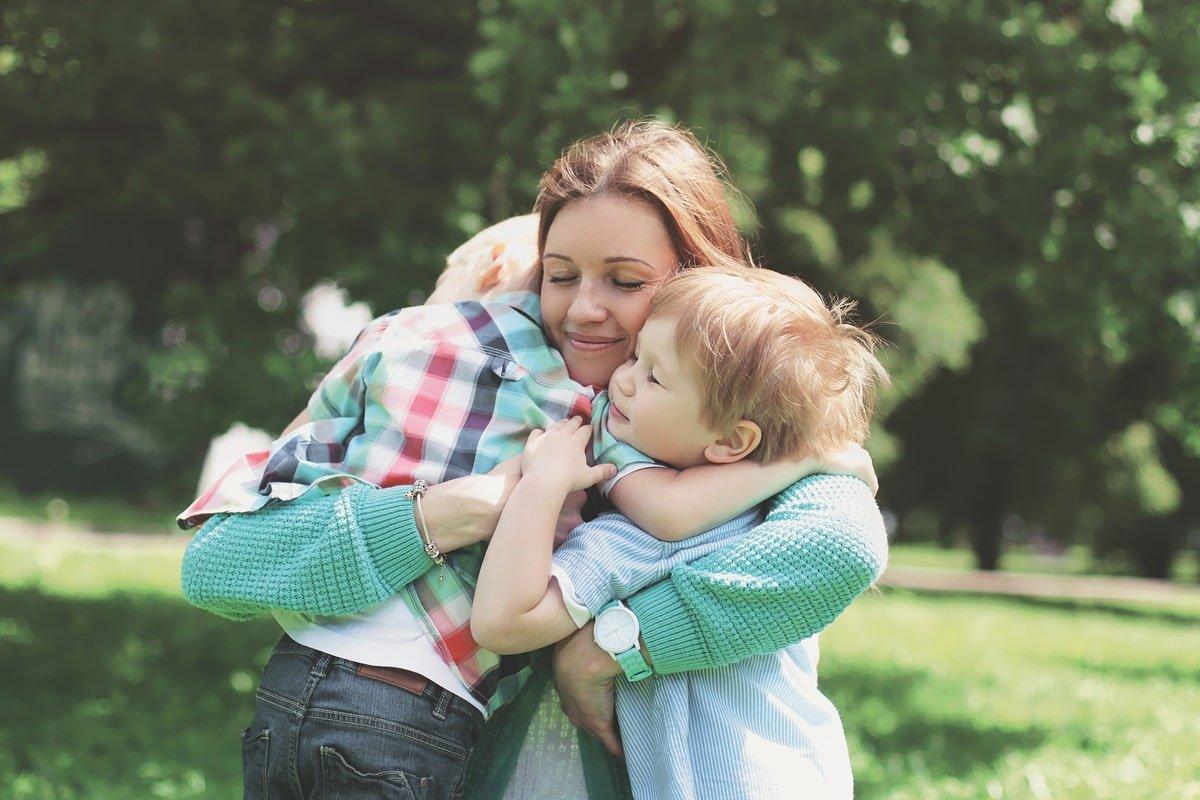 мама обіймає своїх дітей