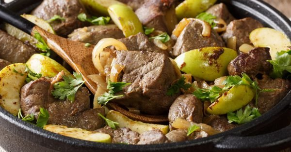 Spicy fried beef liver with apples and onions close-up in a pan on the table. horizontal