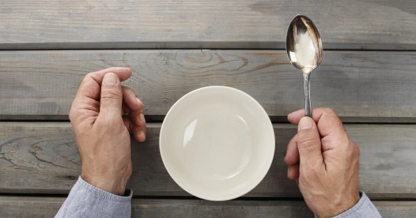 Hungry man waiting for his meal over empty bowl on wooden table.