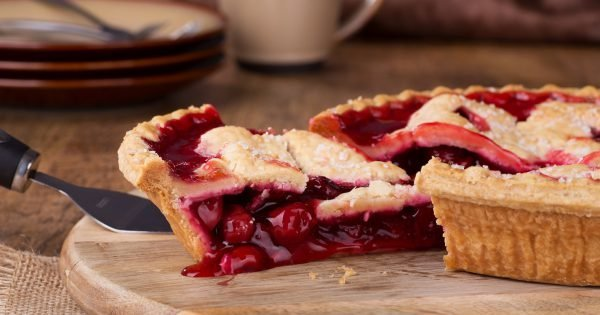 Closeup of a slice of cherry pie on a wooden platter