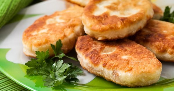 Fried pies on the green dish with sour cream