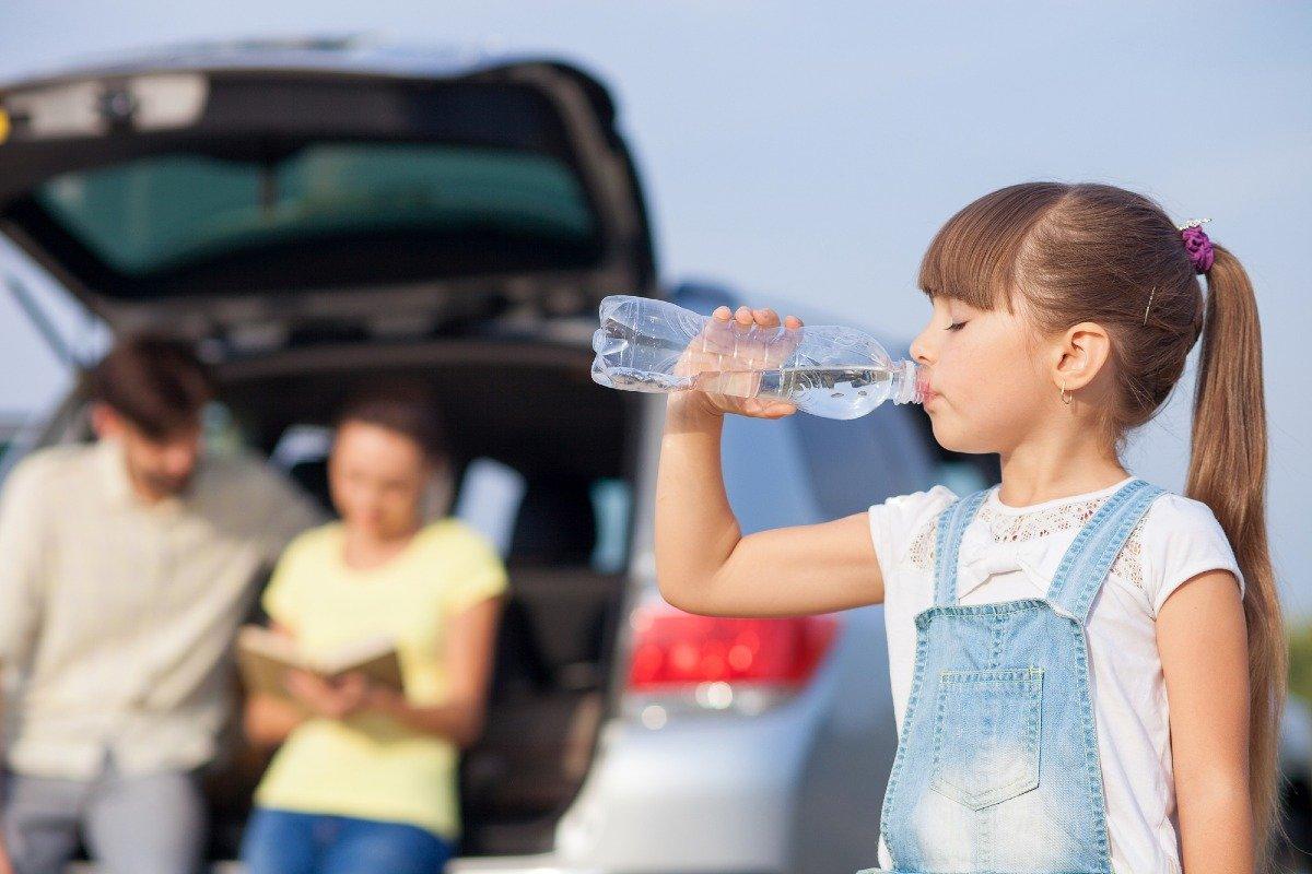 ребенок пьет из пластиковой бутылки