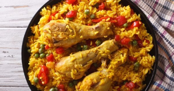 Spanish paella with chicken and vegetables close up on a plate. horizontal view from above