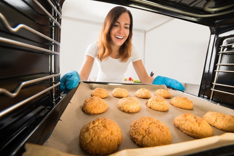женщина вынимает готовое печенье