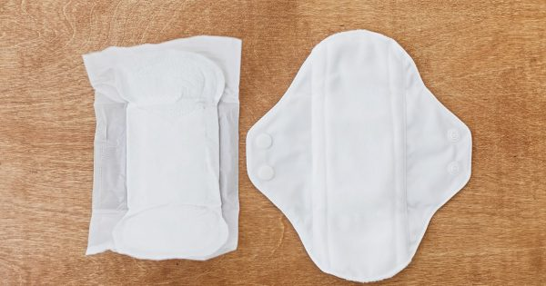 Reusable eco pad and single use toxic pad for menstrual days, flat lay. Chose feminine  healthy and eco friendly pads against plastic pads. Stop plastic pollution. Zero waste lifestyle