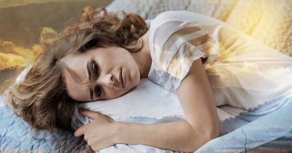 Have a problem. Young female person embracing her pillow while lying on the bed and showing her emotions