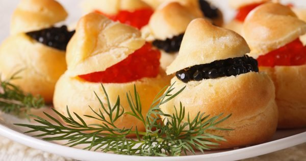 Finger food: profiteroles stuffed with red and black caviar on a plate close-up. horizontal