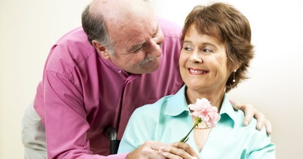 Senior man gives his beautiful wife a flower.