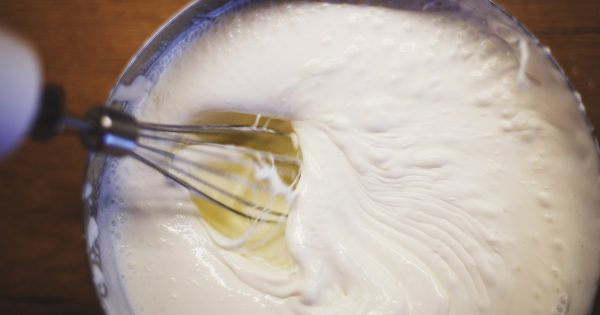 cream is whipped with a mixer in a bowl