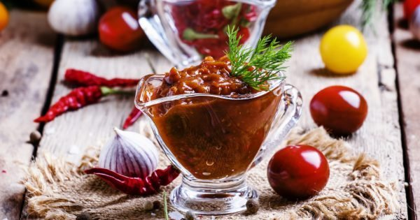 Adjika - traditional Armenian spicy sauce from tomatoes, bell peppers, garlic and spices, vintage wooden background, selective focus