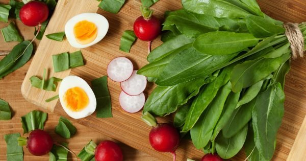 Healthy spring vegetables, sorrel, radish and eggs on wooden table. Super food nutrition.