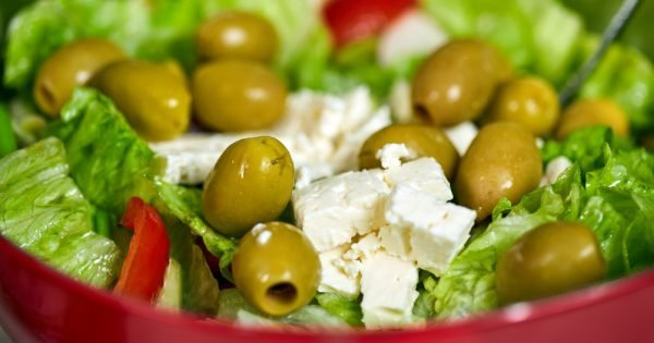 Greek salad with iceberg lettuce, olives, feta cheese and condiments