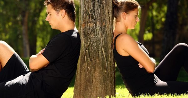 A picture of a young couple sitting in the park and being in a conflict
